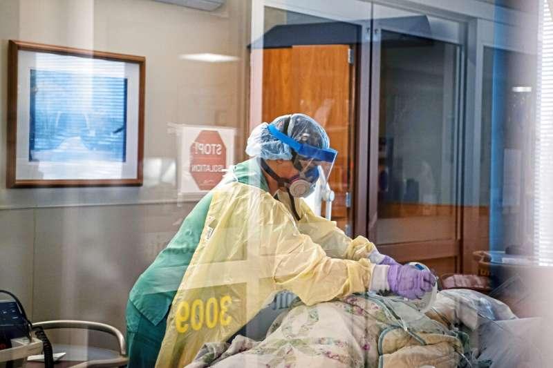 美國賓州尤寧敦的醫護人員正在整理一位新冠死者身上的醫療管線。(美聯社)