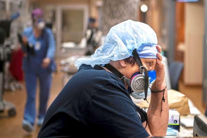 美國賓州尤寧敦醫學中心的半數病房以及加護病房的所有病床,目前收治的都是新冠患者。一位護理師正在緊張繁重的照顧工作中休息片刻。(美聯社)