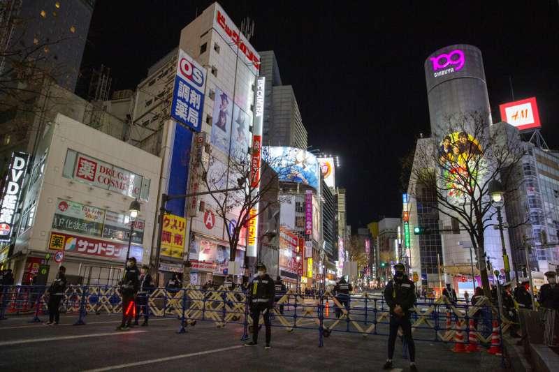 為了避免跨年倒數的人潮聚集,日本警方2020年12月31日在東京澀谷架設拒馬,並且引導民眾離開。(美聯社)