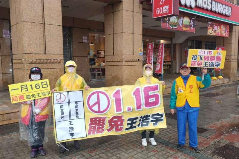 藍營支持者冒著低溫到中壢路口高舉罷免桃園市議員王浩宇宣傳看板與布條。(魯明哲辦公室提供)