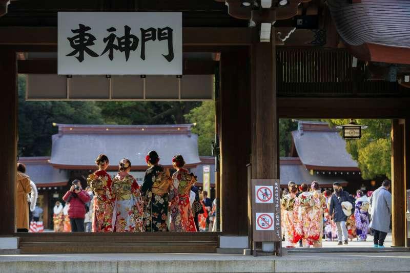 雖然新冠疫情肆虐,東京今年的成人式仍有部分地區維持舉辦,參加者盛裝打扮、戴著口罩出席。(美聯社)