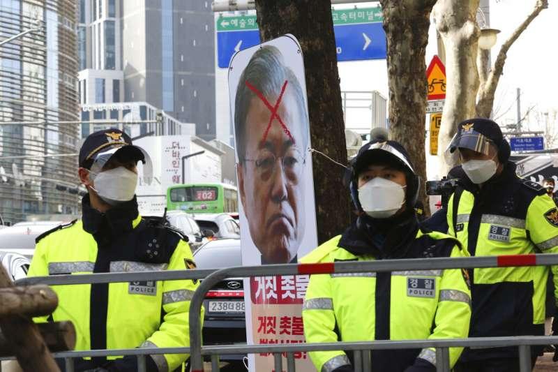朴槿惠的支持者在大法院外舉牌抗議司法不公,甚至將現任總統文在寅的肖像畫上一個大叉叉。(美聯社)