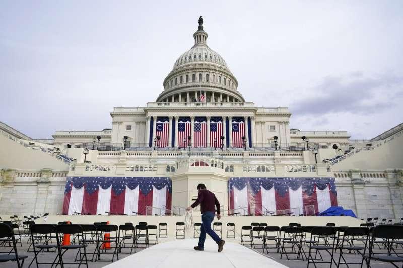 一名工作人員正在國會大廈前整理拜登就職典禮的場地。(美聯社)