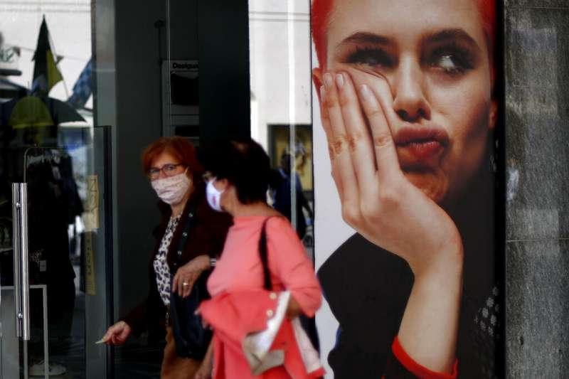 由於疫情嚴重,德國慕尼黑的市民在逛街購物時也紛紛戴上口罩。(美聯社)