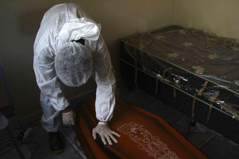 新冠病毒在巴西亞馬遜州首府瑪瑙斯(Manaus)嚴重肆虐,當地的葬儀人員為一名在家中病逝的77歲感染者收屍。(美聯社)