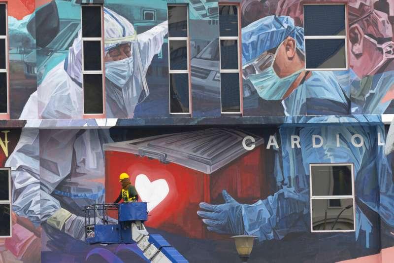 馬來西亞吉隆坡一間醫院的外牆,畫上了醫護人員與疫情奮戰的景象。(美聯社)