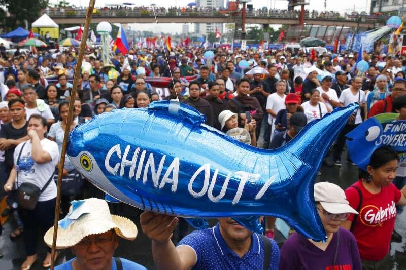 反對中國擴張南海霸權的菲律賓民眾,2019年在馬尼拉的國會大廈外群聚抗議。示威者高舉一個鯊魚氣球,上頭寫著「中國滾蛋」。(美聯社)