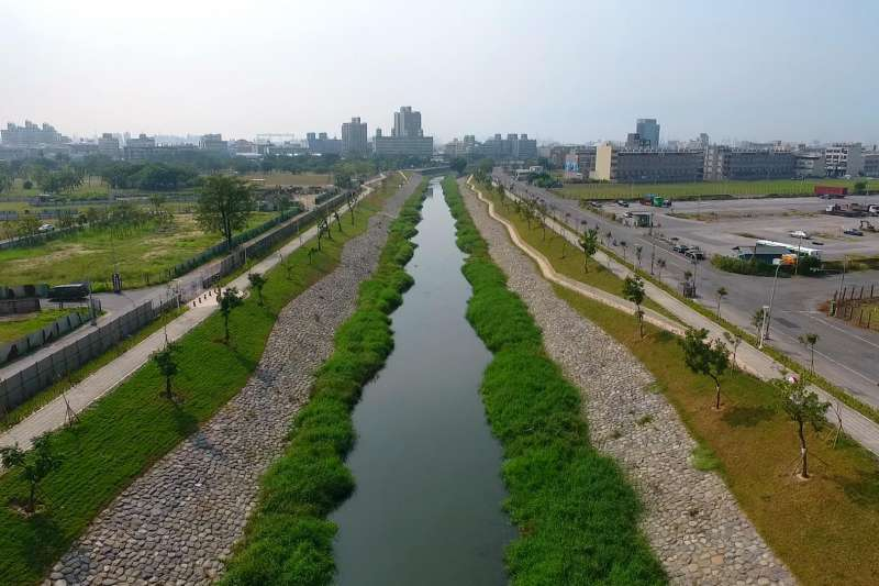 鳳山溪民安橋下游河岸原大量使用混凝土興築護岸作為防水建造物,因此喪失原自然生態景觀風貌。(圖/高雄水利局提供)