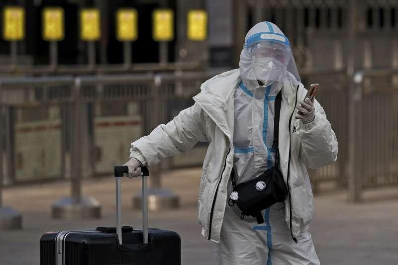 2021農曆新年:中國旅客身穿防護服,避免感染新冠病毒。(AP)