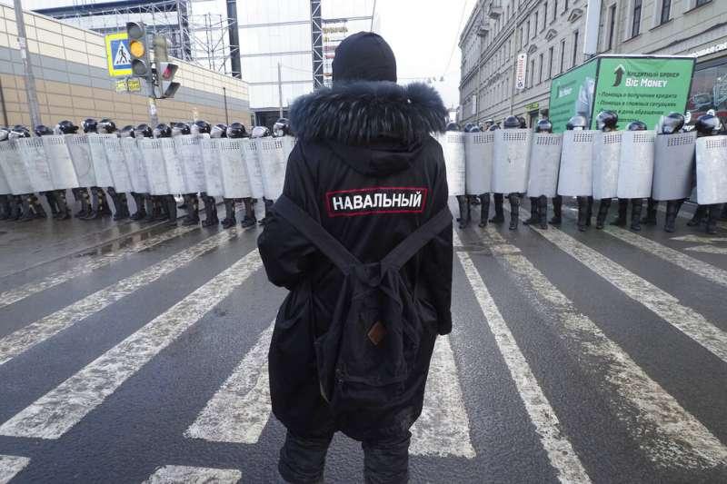 俄國一位示威者將納瓦爾尼的姓名繡在身後,在聖彼得堡的街頭與警方對峙。(美聯社)