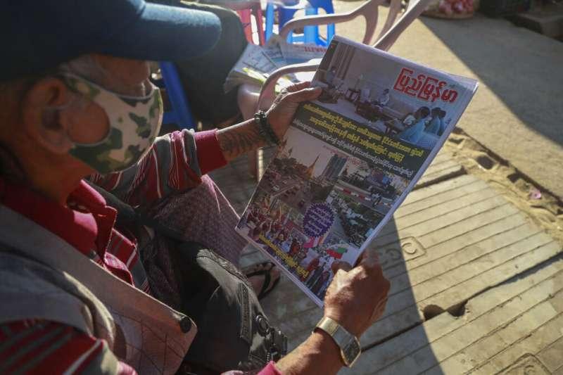 緬甸軍方發動政變後,仰光一位民眾正在端詳報紙頭條的「緬甸進入緊急狀態」報導。(美聯社)