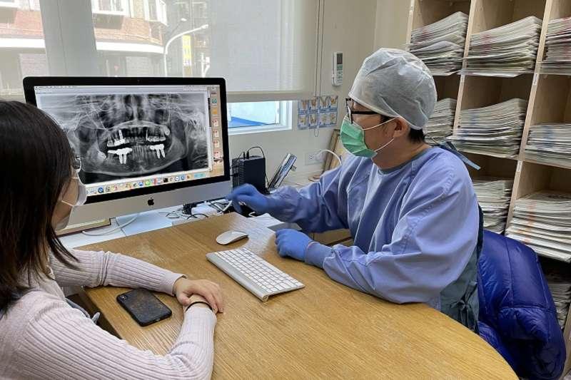 瑞比牙醫診所院長張箭球向患者解釋 X 光片,評估植牙方式(圖片來源:瑞比牙醫)