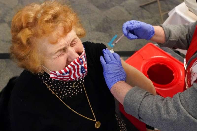 美國麻省一位婦人正在接受新冠疫苗注射。(美聯社)