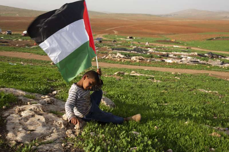 2021年2月3日,以色列軍隊拆除了約旦河谷的貝都因人帳篷和其他建築物後,一名巴勒斯坦的貝都因男孩舉起一面巴勒斯坦國旗。(美聯社)