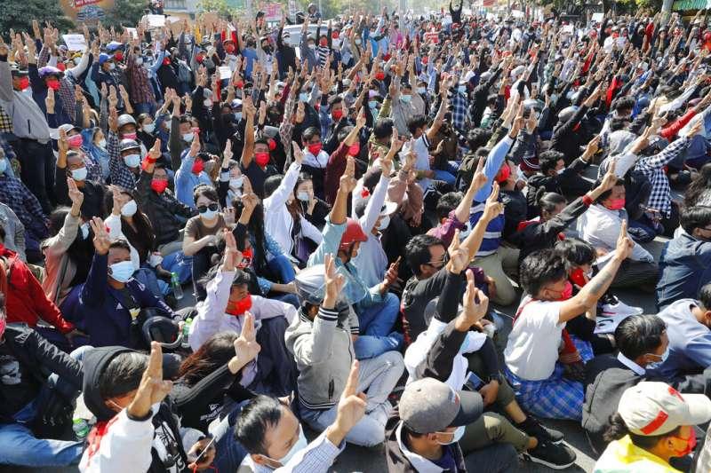 緬甸大城曼德勒的示威者9日與警方在街頭對峙,並且高舉三指表達抗議。(美聯社)