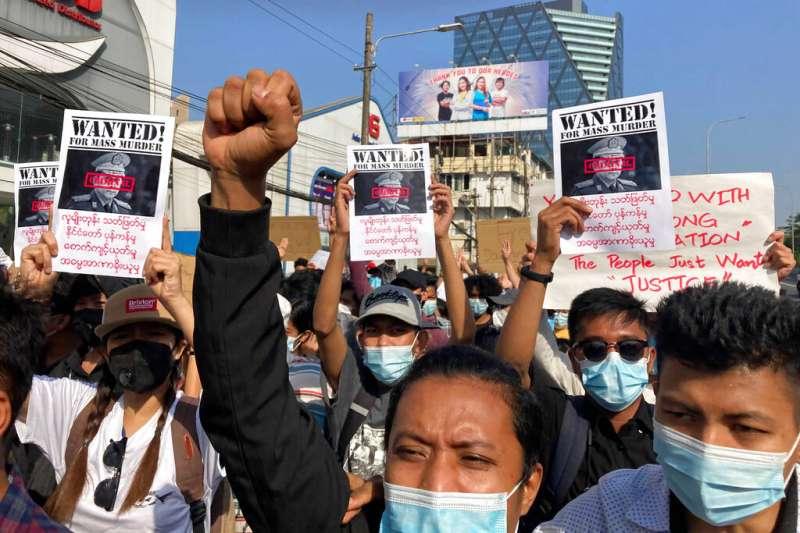 仰光的抗議者高舉「通緝敏昂萊」的傳單,要求緬甸軍政府立刻歸還政權。(美聯社)