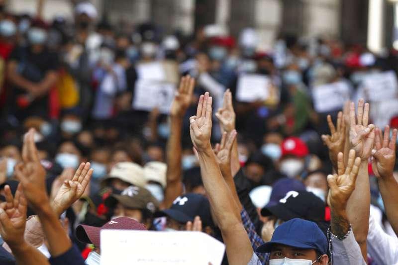 仰光的抗議者高舉三指,要求緬甸軍政府下台。(美聯社)