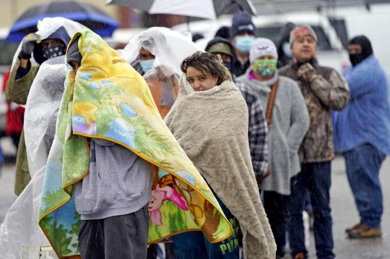美國德州遭遇百年來最嚴重冬季暴風雪侵襲,當地民眾飽受停電、停水之苦,紛紛上街排隊領取罐裝天然氣取暖。(AP)