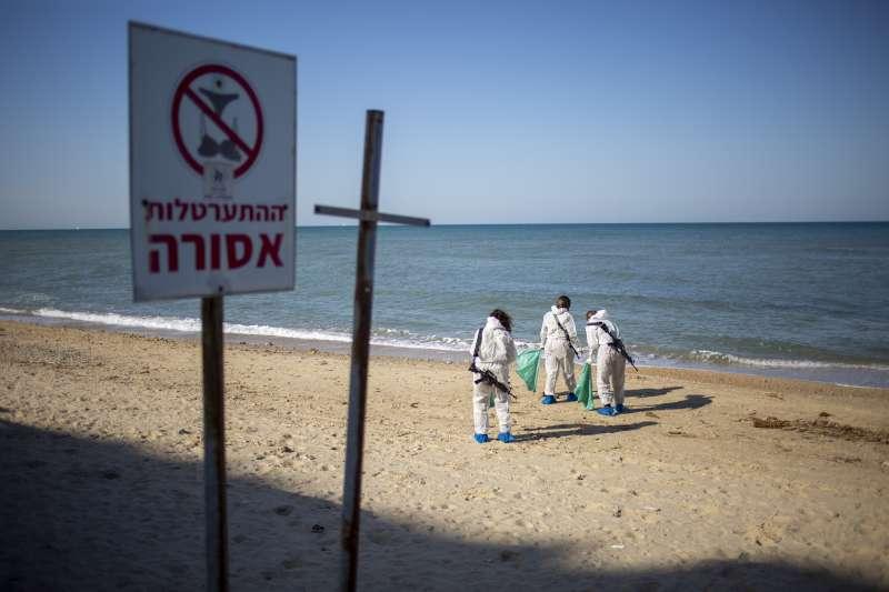 地中海東岸發生漏油事件。以色列海灘上,環保人士全副武裝清理焦油。(美聯社)