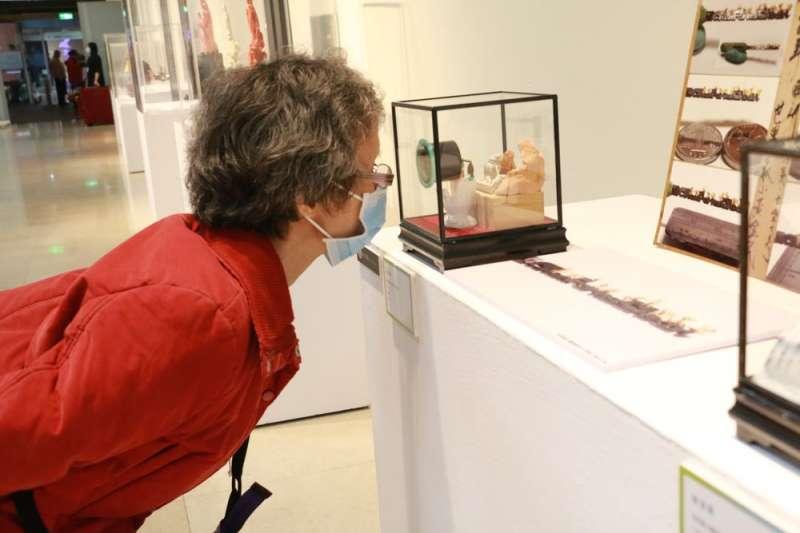 民眾觀看陳逢顯老師作品「世界最小雕刻黃金小老鼠」。(圖/李梅瑛)