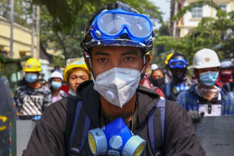 緬甸軍隊、緬甸軍政府、緬甸示威、緬甸政變。緬甸街頭勇於對抗鎮壓的示威者,頭戴安全帽,手持自製盾牌。(AP)