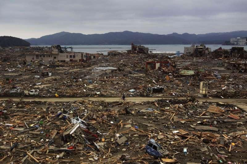 311浩劫十周年。福島核災。圖為2011年4月,倖存者騎單車進入受災的南相馬市。(AP)