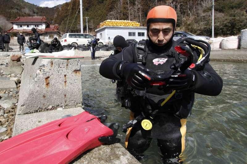 日本311浩劫十周年,64歲的高松康夫多年潛入海底,尋找愛妻蹤影。(AP)