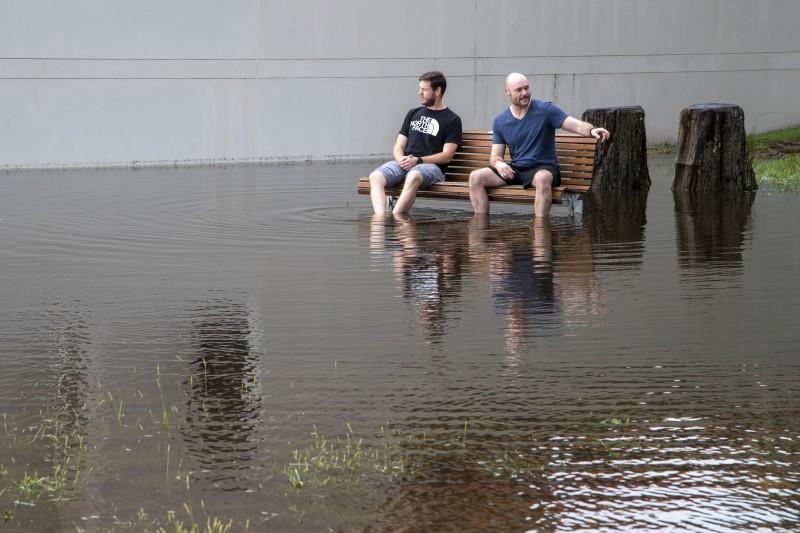 澳洲雪梨以北史蒂芬斯港地區,兩名男子坐在淹水的公園內(美聯社)