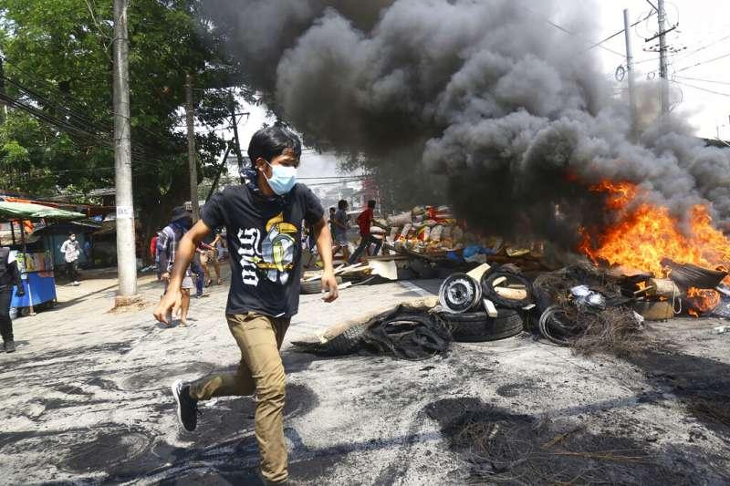 緬甸的反政府抗爭者28日在仰光街頭焚燒輪胎與雜物,構築與軍警對峙的防線。(美聯社)