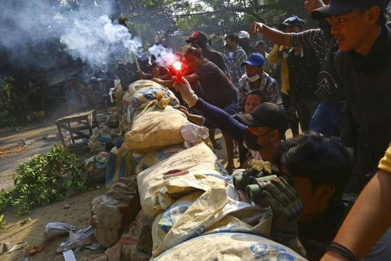 緬甸的反政府抗爭者28日在仰光街頭準備丟擲汽油彈。(美聯社)