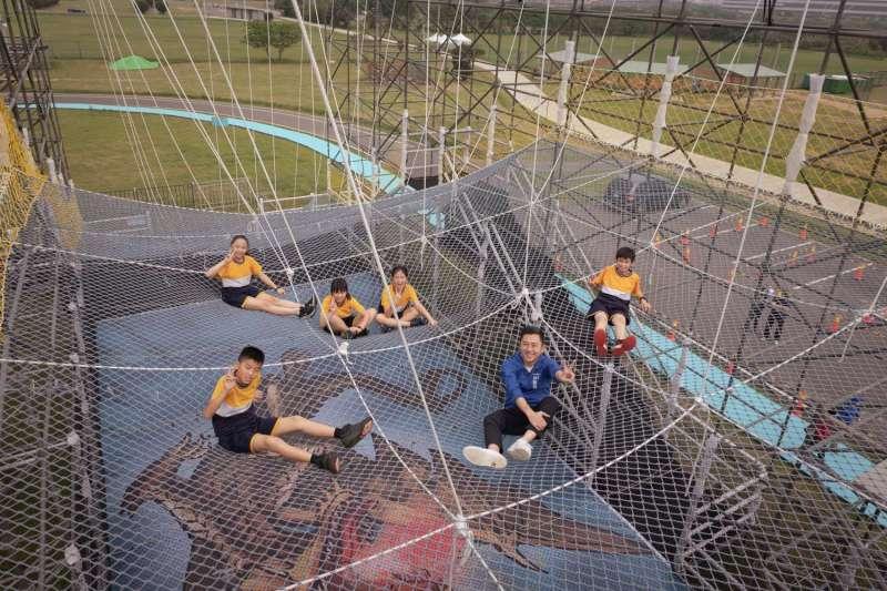 林智堅與孩子體驗遊具,爬到「漫步雲端」10公尺最高處模擬「躺在雲朵上」的滋味。(圖/新竹市政府提供)