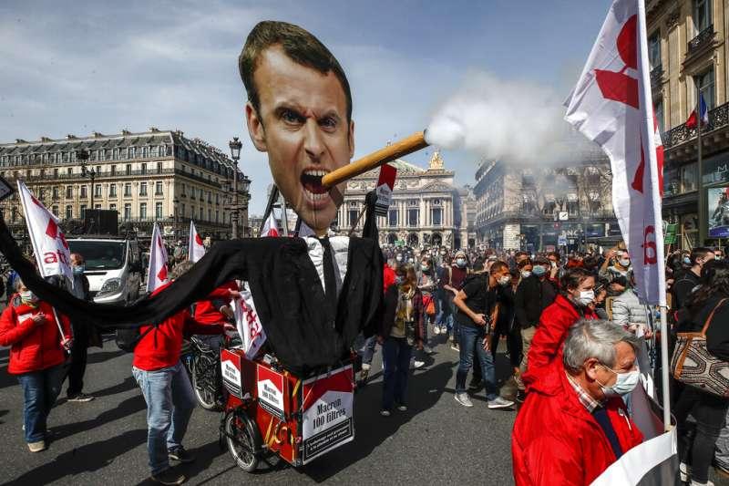 巴黎街頭反對氣候變遷的抗議遊行,人潮裡出現法國總統馬克宏大抽雪茄的肖像。(資料照,美聯社)