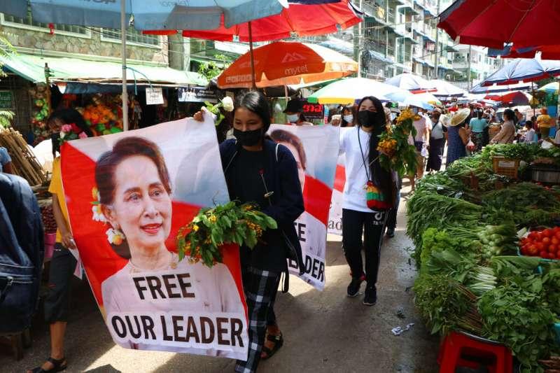 反對緬甸軍政府發動政變的民眾,在仰光街頭高舉遭軟禁的翁山蘇姬照片,呼籲軍政府盡快放人。(美聯社)