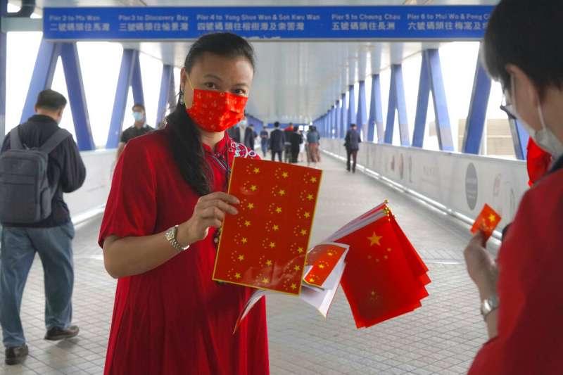 香港的親中人士於「全民國家安全教育日」在街頭分送中國國旗。(美聯社)