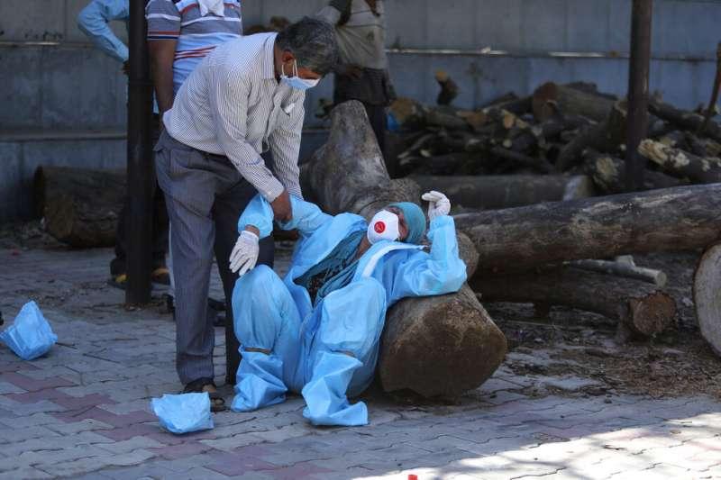 印度第二波疫情席捲全國,一位死者家屬在送葬的過程中悲痛難抑。(美聯社)