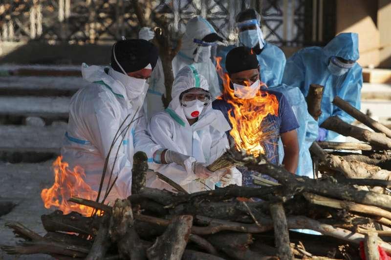 死亡病例湧入讓印度的火葬場不堪負荷,遺體與家屬只得排隊等候。(美聯社)
