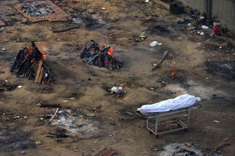 印度新一波疫情來勢洶洶,每日急遽增加的死者讓火葬場難以負荷。圖為一具正在排隊等待焚化的死者屍體。(美聯社)