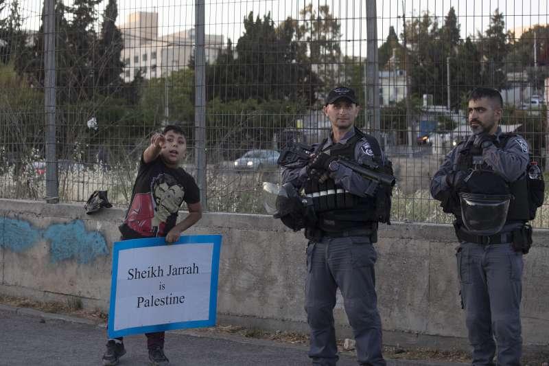 以色列員警和手持「謝克賈拉區屬巴勒斯坦」標語的男孩(AP)
