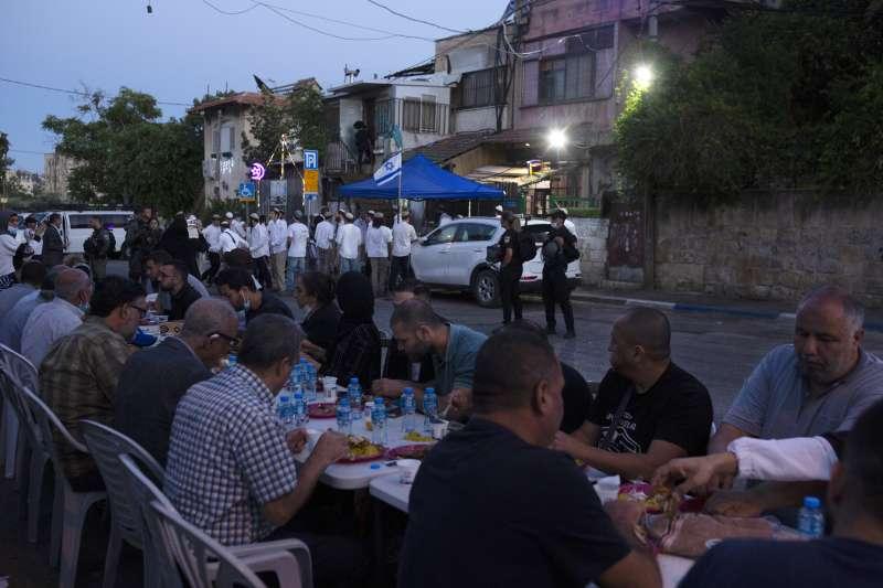 巴勒斯坦裔日落後進食,同街另一邊是猶太人屯墾機構的人(AP)