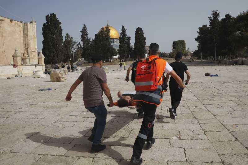 10日,巴勒斯坦人與以色列警察在耶路撒冷舊城的阿克薩清真寺爆發衝突,巴勒斯坦人緊急抬走一名受傷男子(美聯社)