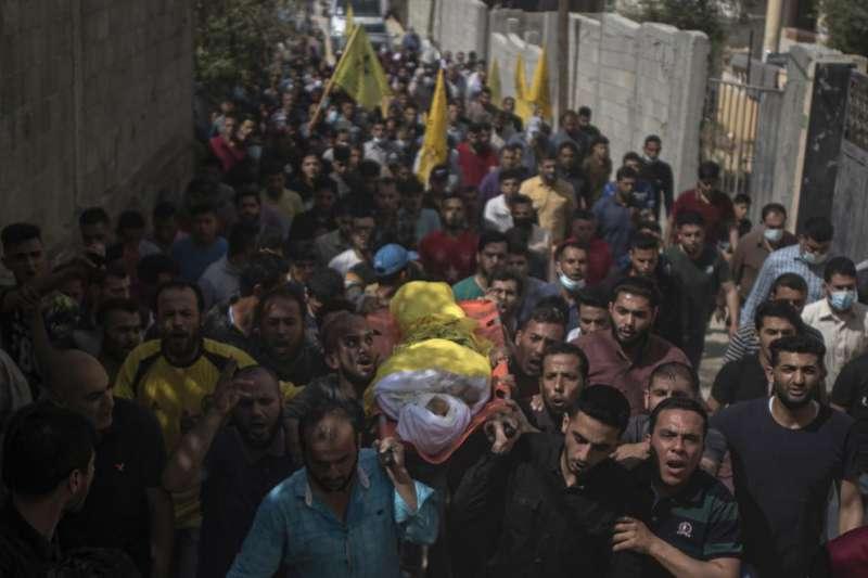 以巴衝突、以色列空襲加薩走廊,一名死於砲擊的巴勒斯坦男童遺體被眾人抬起。(AP)