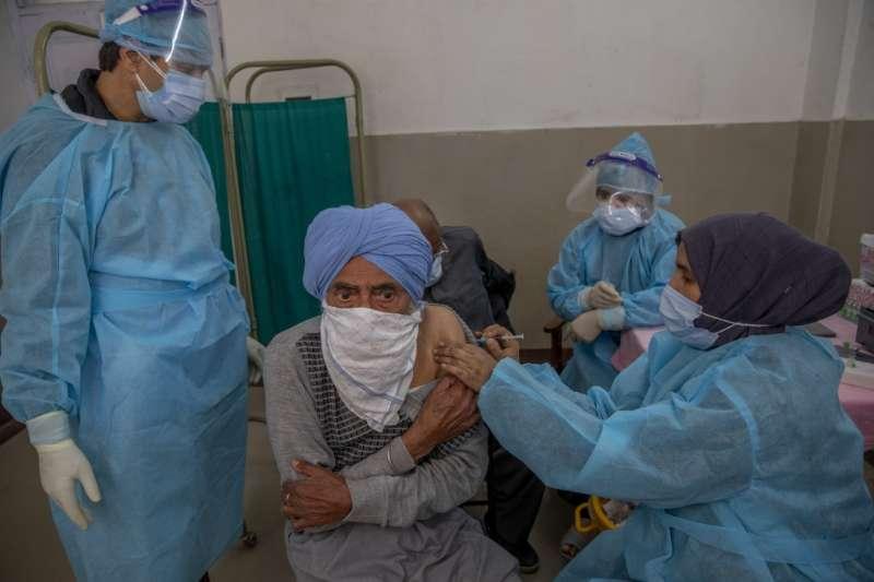 4月28日,印屬喀什米爾首府斯利那加,一名老人正接種新冠疫苗Covishield(美聯社)