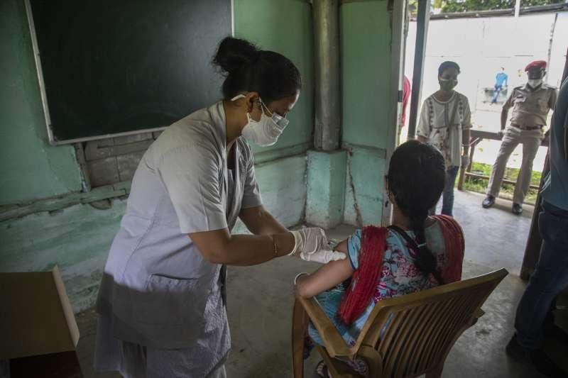 5月10日,印度阿薩姆邦第一大城古瓦哈提,醫護人員正幫民眾施打新冠疫苗Covaxin(美聯社)