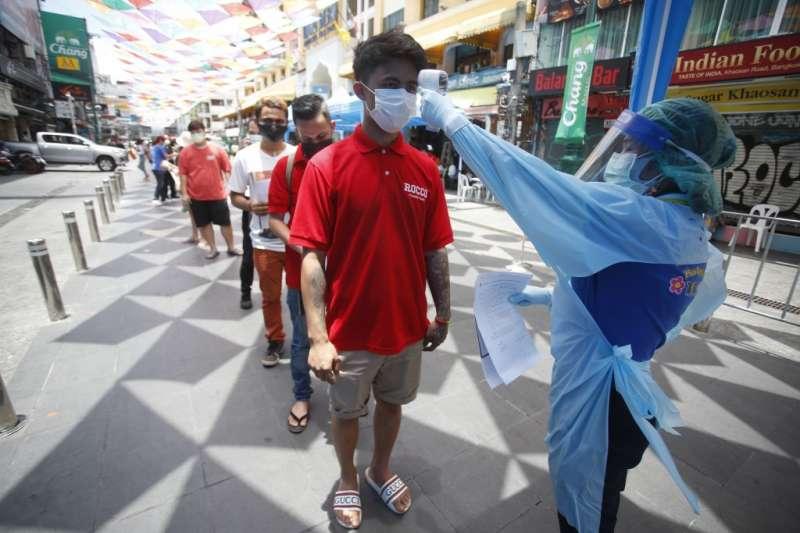 4月14日,泰國曼谷,醫護人員為排隊等待新冠肺炎篩檢的人們測量體溫(美聯社)