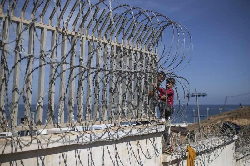 2021年5月18日,西班牙海外領土休達市湧入8000位移民,多數都是摩洛哥人。圖為一名兒童嘗試越過柵欄。(AP)