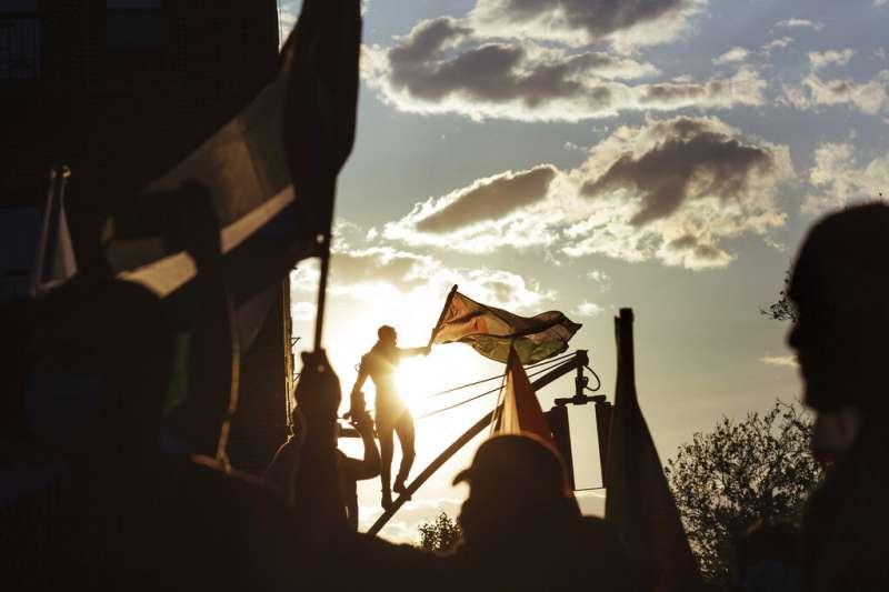 巴勒斯坦人在紐約的夕陽之下揮舞旗幟,抗議以色列對祖國的侵略。(美聯社)