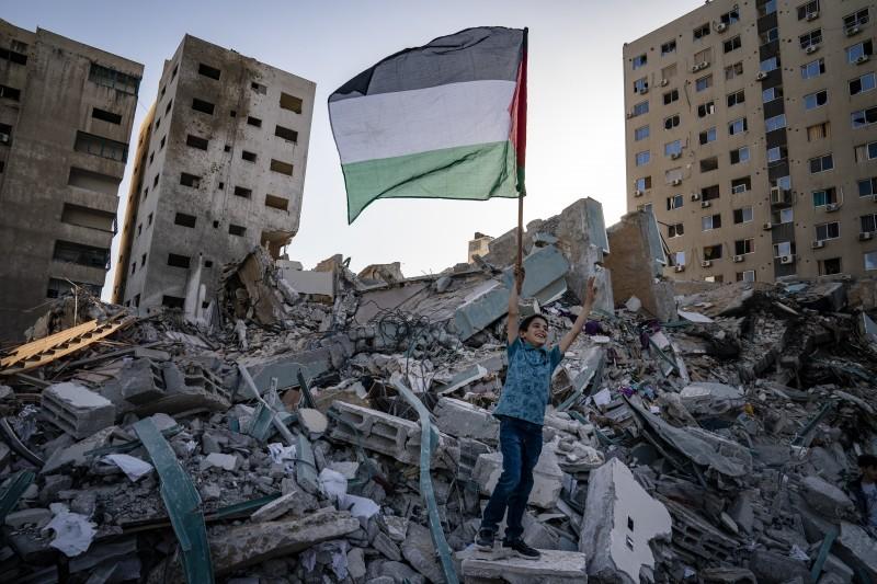 2021年5月21日,以色列與巴勒斯坦激進組織哈瑪斯停火,加薩走廊1名男孩在遭炸毀的瓦礫中高舉巴勒斯坦國旗(AP)