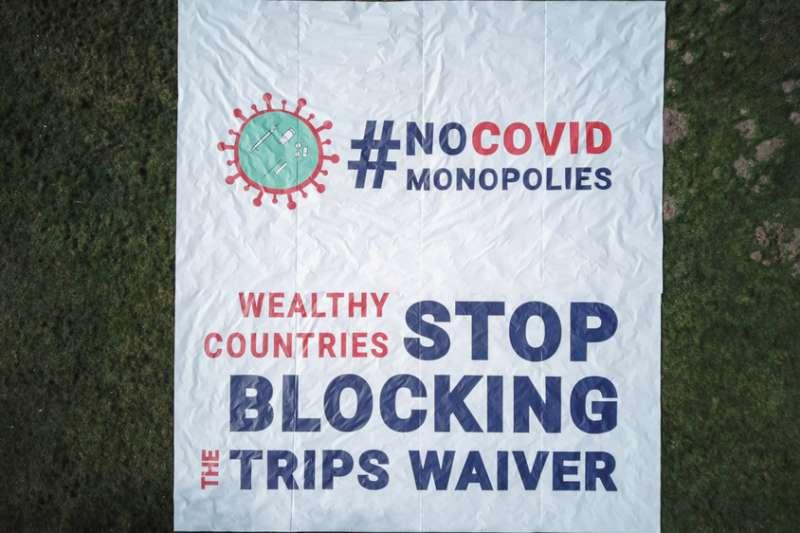 無國界醫生在日內瓦世界貿易組織(WTO)前展開的橫額,呼籲多個政府在大流行期間停止阻礙知識產權豁免議案。(Pierre-Yves Bernard/MSF)