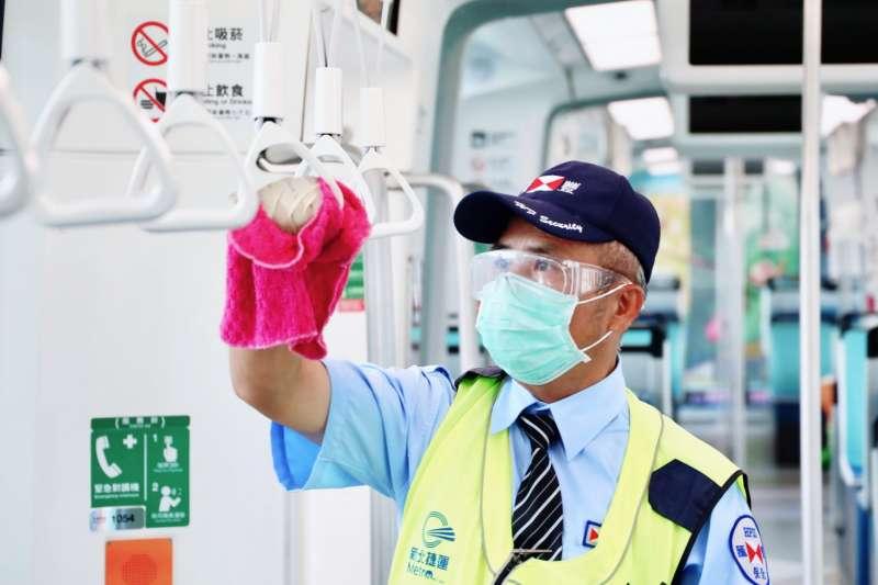 20210527-淡海輕軌第一線執勤人員認真地消毒車廂吊環。(新北捷運公司提供)