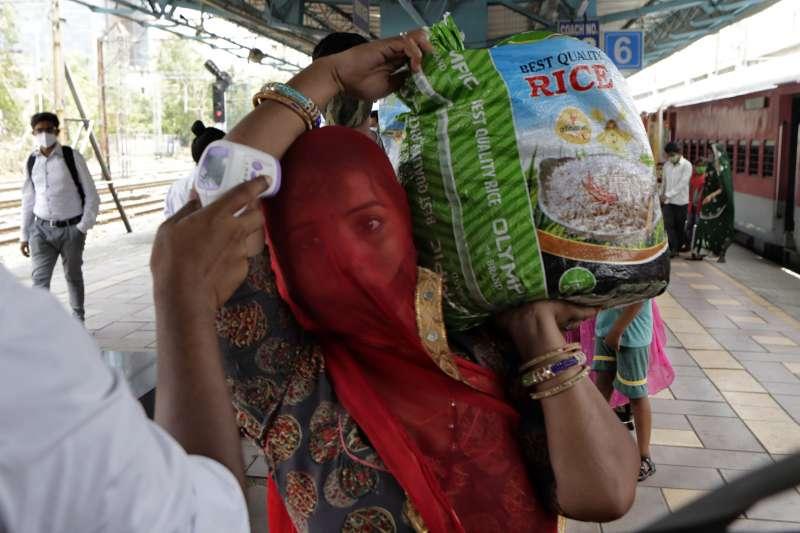 印度新冠疫情趨緩。孟買火車站的站務員為乘客量測體溫。(AP)